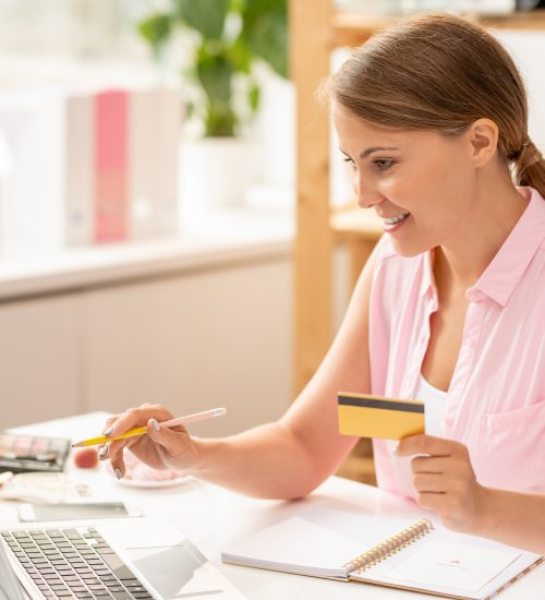Happy young female shopaholic with plastic card pointing at laptop display while choosing online goods
